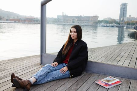 brunnet: Attractive young tourist girl sitting on wooden pier enjoying beautiful view of Barcelona port Stock Photo