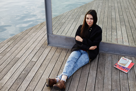 brunnet: Charming asian student girl sitting on wooden pier during her class break at university