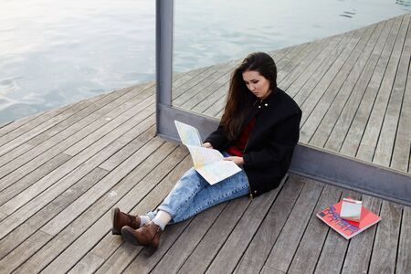 brunnet: Young asian tourist woman look city map sitting on wooden pier, stylish tourist girl resting after long walk in new country studying a map Stock Photo