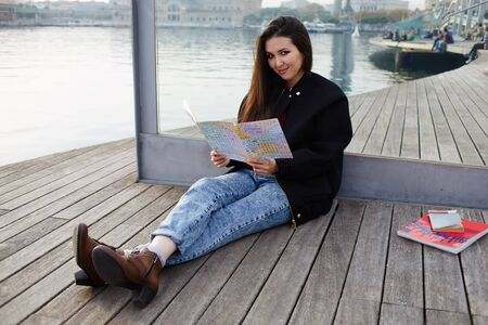 Attractive tourist girl resting after walk sitting on wooden pier in sea port, beautiful student girl holding city map in hands smiling, charming asian girl sitting with open city map on wooden pier Stock Photo