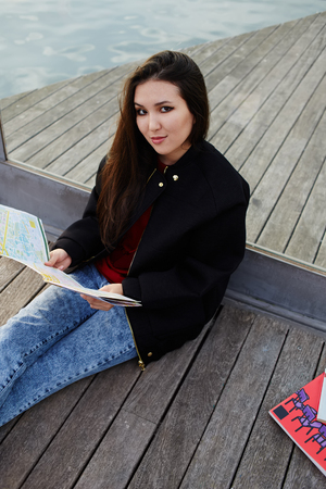 Portrait of charming asian race girl sitting with the map on wooden pier, attractive tourist girl resting after walk sitting on wooden pier in sea port,portrait of beautiful student girl with city map