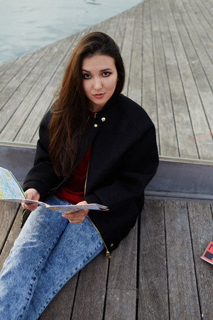brunnet: Portrait of charming asian race girl sitting with the map on wooden pier, attractive tourist girl resting after walk sitting on wooden pier in sea port,portrait of beautiful student girl with city map