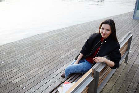 Attractive student girl seated on wooden bench having class break, female tourist woman with smile looking to the camera, stylish hipster girl posing outdoors Stock Photo