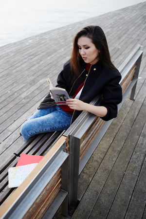 Young asian race woman read the book sitting on wooden bench, charming student girl concentrated reading some book outdoors, stylish tourist girl resting after long walk in new country