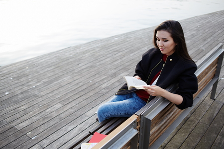 brunnet: Asian student girl reading book seated on the bench, attractive college student reading book during her class break outdoors, young woman reading book on the wooden bench
