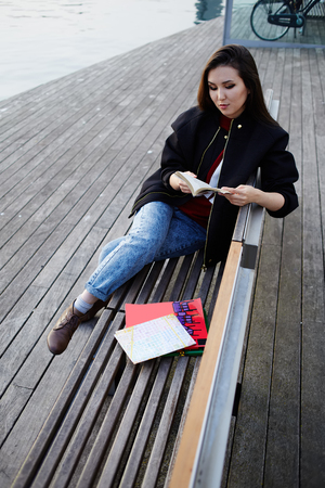 brunnet: Vacation holiday in Barcelona, young female traveler sitting on wooden bench read some book, Chinese student girl reading book sitting in sea port on wooden pier, travel and leisure concept Stock Photo