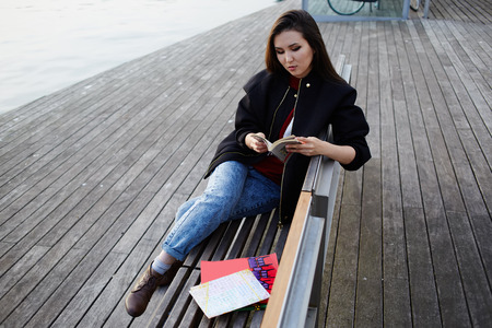 brunnet: Attractive female student reading a book outdoors, beautiful girl holding an open book sitting on wooden bench near artificial lake, tourist woman resting after walk in new city reading some book