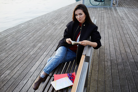 brunnet: Beautiful girl holding an open book sitting on wooden bench near artificial lake, tourist woman resting after walk in new city reading some book, attractive asian girl at leisure time outdoors