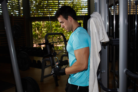 lat: Muscular build athlete working out with lat machine dumbbells at gym