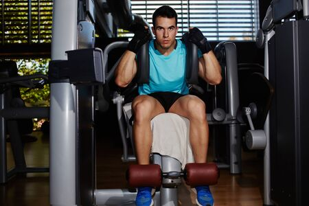 abdominal muscles: Young athletic man exercise with abs muscles on press machine, handsome fit man working out with abdominal muscles Stock Photo