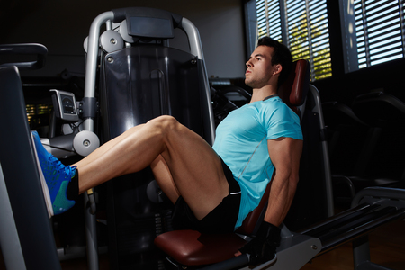 muscular build: Full lengt portrait of muscular build man doing legs press exercise in fitness center