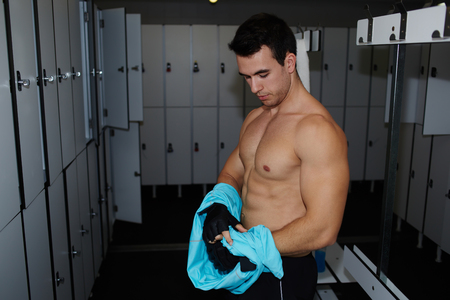 muscular build: Handsome muscular build man removing t�shirt standing in gyms locker room after workout
