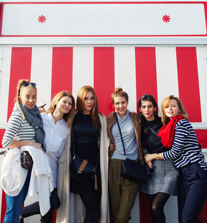 sorority: Outdoor portrait of beautiful group of women having fun and smiling against fair decoration