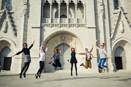 sorority: Portrait of a lively excited women jumping in air against building, enjoying holidays, group of girlfriends outdoors having lots of fun jumping around