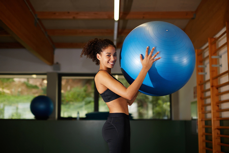 fit ball: Young cheerful afro woman standing with fit ball in fitness center, attractive afro girl with curly hair smiling at gym
