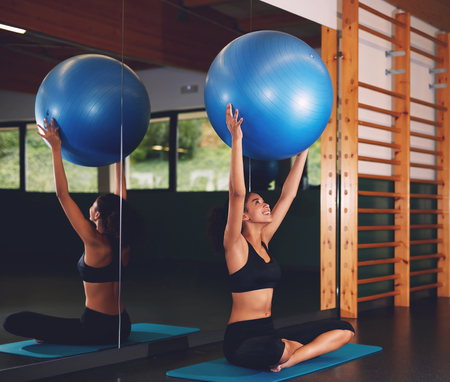 healthy sport: Young athletic woman sitting on the mat with Pilates ball against big fitness hall mirror