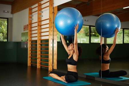 balance ball: Charming afro american girl holding up balance ball and enjoying time at gym, young fit woman looking so happy