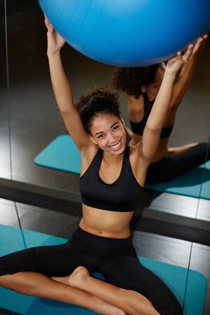 balance ball: Portrait of radiant young woman holding up balance ball and looking to the camera with brilliant smile, young happy woman enjoying time at fitness class at gym