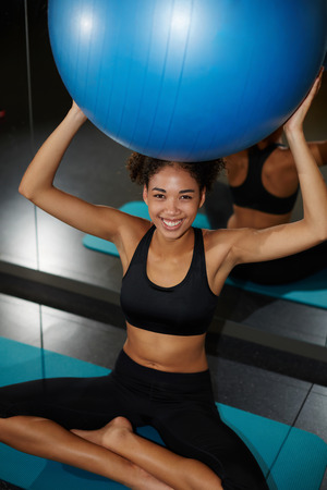 balance ball: Beautiful young woman enjoying time at the gym, cheerful afro woman laughing while hold balance ball in health center, a radiant young black woman smiling brightly at Pilates class