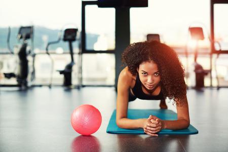 Jeune femme séduisante travaillant avec des muscles abdominaux au gymnase Banque d'images