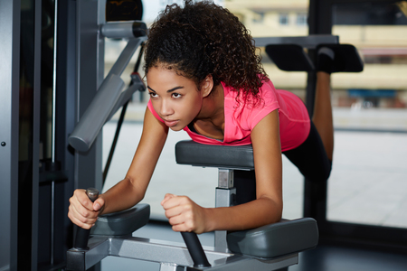 attainment: Attractive fit girl with curly afro hair working out with buttocks muscles on weights machine at gym Stock Photo