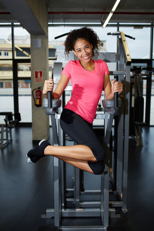 girl working out: Attractive dark skinned girl working out for abs muscles at gym