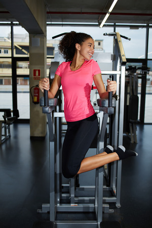 dark skinned: Full length portrait of happy fit woman exercising her abdominal muscles for beautiful figure, attractive dark skinned girl feeling so happy working out