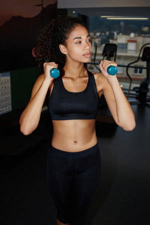 free weights: Portrait of young fitness woman doing workout with free weights at gym, attractive fit girl dressed in sportswear working out with dumbbells