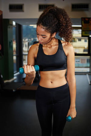 free weights: Portrait of young fit woman working out with free weights at fitness center, attractive afro american girl lifting dumbbells at gym Stock Photo