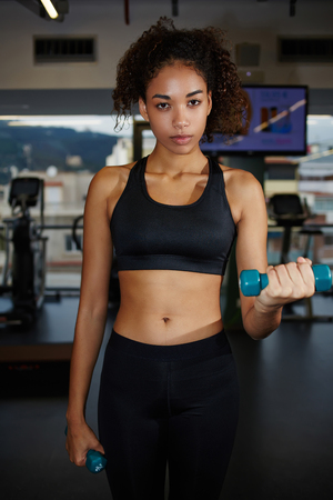 free weights: Portrait of young afro woman exercising with free weights at fitness center, attractive young woman working out with dumbbells Stock Photo