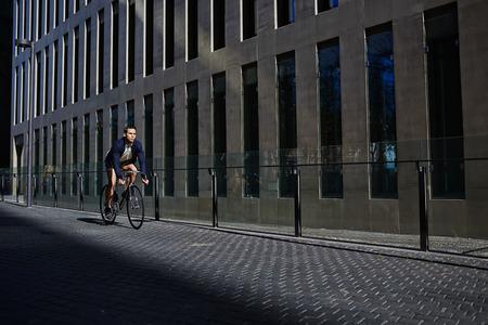 clavados: Hombre con estilo inconformista que monta en bicicleta de piñón fijo, joven del paseo el hombre hermoso en bicicleta en la zona moderna de la ciudad, paseo hombre joven y atractiva en bicicleta fija del engranaje que mira lejos