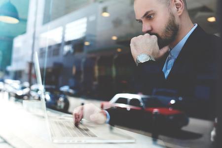 자신감이 잠겨있는 사업가의 창을 통해 볼 때 뉴욕시의 도시 커피 숍에 앉아있는 동안 휴대용 netbook을 통해 주식 시장의 주식을 모니터링하고 있습니