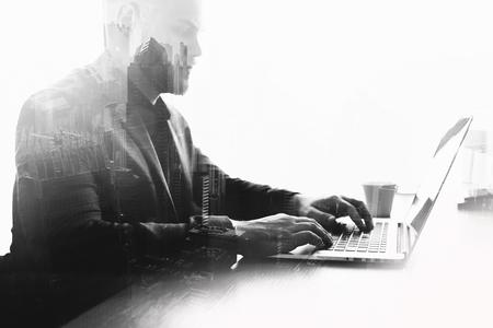 深刻な若者の成功したトレーダーとダブル黒と白の露出効果は、パソコンを介して取引を監視されています。熟練した実業家は、ネット書籍に取り 写真素材