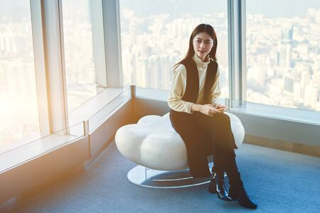 Asian female is using cell telephone, while is waiting beginning of interview with experts in the economic field. Businesswoman is sitting in office of successful company against big skyscraper window