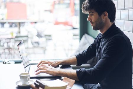 랩톱 컴퓨터와 와이파이 연결을 사용하여 문학에 영감을 불어 넣은 후 웹 사이트에 새로운 책 리뷰의 텍스트를 입력 스톡 콘텐츠