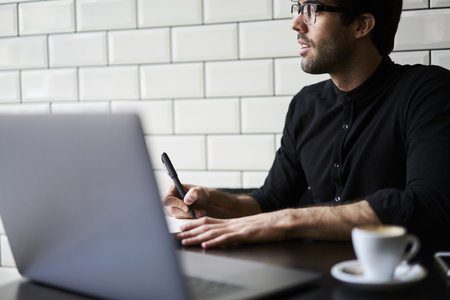 Thinking over his reportage writing down best ideas into notebook creating article for publication working hard in morning sitting in modern coffee shop interior Stock Photo