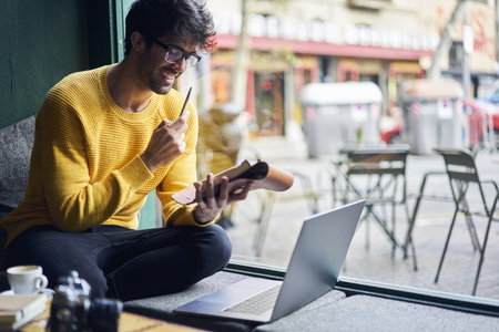 Write Ideas into personal organizer starting working day with cup of coffee sitting with laptop in cafe using free wireless connection to network Banque d'images