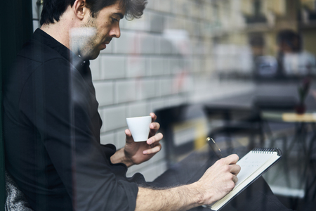 Publication starting his working day in cafe with cup of coffee for breakfast inspiring good weather outdoors while sitting near window checking his new text