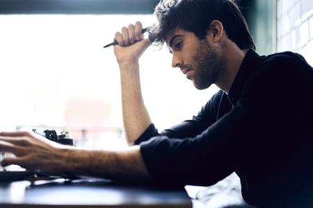 Journalist die over zijn reportage denkt die beste ideeën opschrijven in notitieboekje die artikel voor publicatie creëren die hard in ochtend werken die op kantoor zitten