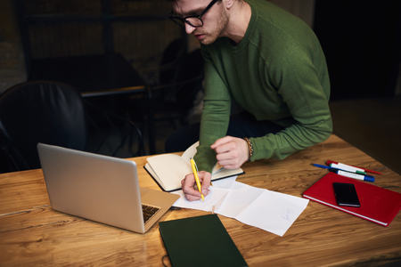 Thoughtful male student working on coursework writing report for presentation watching training webinar for completing task, skilled journalist working overtime in studio preparing press release Stock Photo