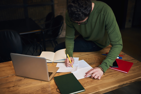 Talented male journalist working in studio preparing article for publication using information from web, student creating coursework learning and solving problems writing composition in notebook