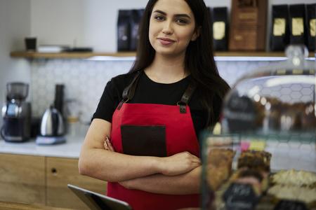 Ritratto di attraente barista femminile che lavora come cameriera vicino a una barra pronta a registrare ordini dai clienti e fare caffè aromatico utilizzando attrezzature moderne, vendendo deliziosi bigné e dessert