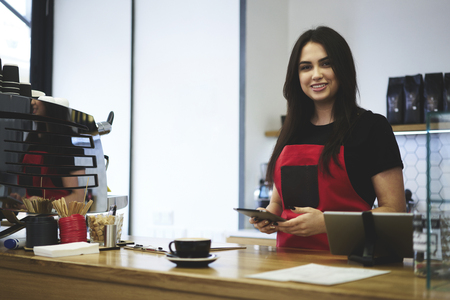 Charming young female barista making ordering for production using application on tablet connected to wireless internet in cafeteria, professional waitress making money transfer for purchasing Stok Fotoğraf