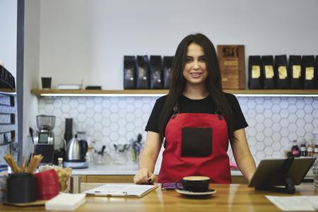 Ritratto di attraente sorridente barista femminile che lavora in caffetteria in buon umore in attesa di ordinare vestito in grembiule, affascinante cameriera sensazione emozionante godersi il giorno lavorativo in caffè con gadget