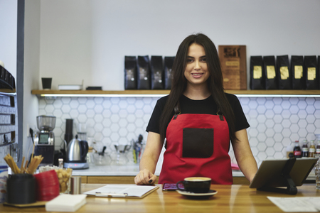 Portrait of attractive smiling female barista working in cafeteria in good mood waiting for ordering dressed in apron, charming waitress feeling exciting enjoy working day in coffee shop using gadgets