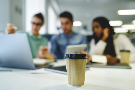 Selective focus on paper coffee cup standing on wooden table in coworking office during lunch break on blurred background with working people silhouettes sitting at desktop with modern technology Imagens
