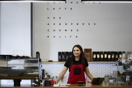 Sorridente attraente cameriera in piedi vicino a bar in uniforme in attesa di clienti in modern loft interno caffetteria, affascinante femminile barista godendo di lavorare in un negozio di caffè con attrezzature