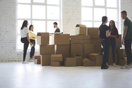 Jonge mannelijke en vrouwelijke collega's hipsters verhuisd naar nieuw kantoor appartement praten maken van plannen voor het uitpakken van dozen met personeel, groep collega's met gesprek beslissen hoe ontwerpruimte Stockfoto