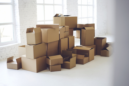 Carton boxes full of office goods stacked in new white loft interior, relocation in new flat. Delivery or packaging service. Cardboards with mock up copy space for brand company information or logo