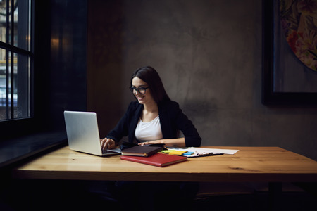 Making distance work sitting in modern interior office, smiling businesswoman satisfied with financial report on laptop